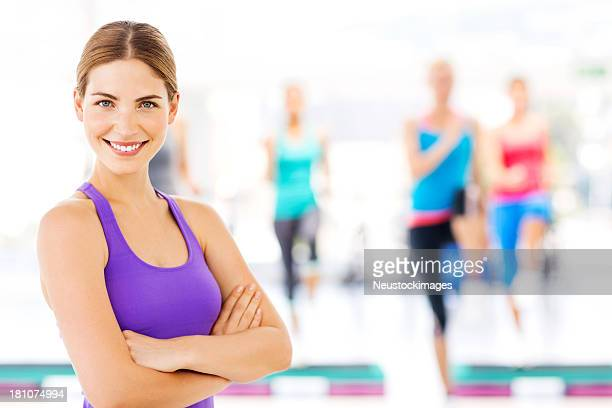 Instructor Standing Arms Crossed With Fitness Class At Gym