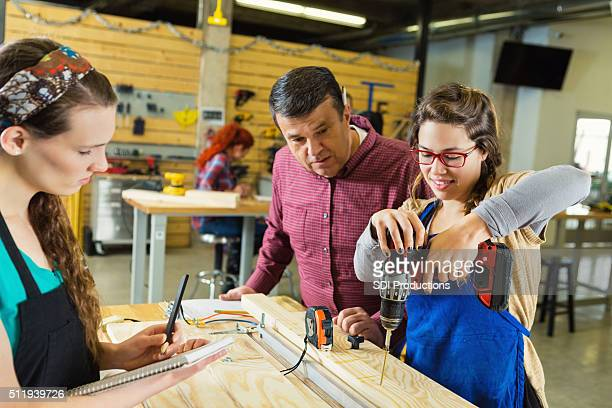 Instructor teaching college age students in makerspace woodworking shop