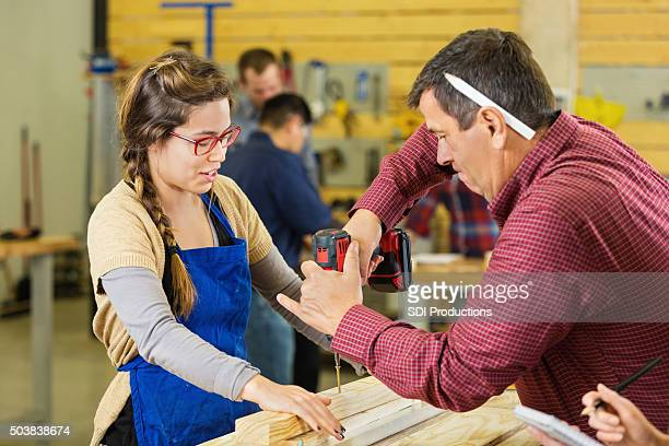 Instructor teaching college student to build something in woodworking class