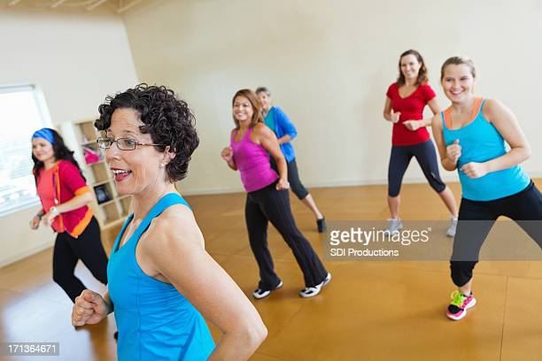 Instructor teaching group of healthy women dance fitness