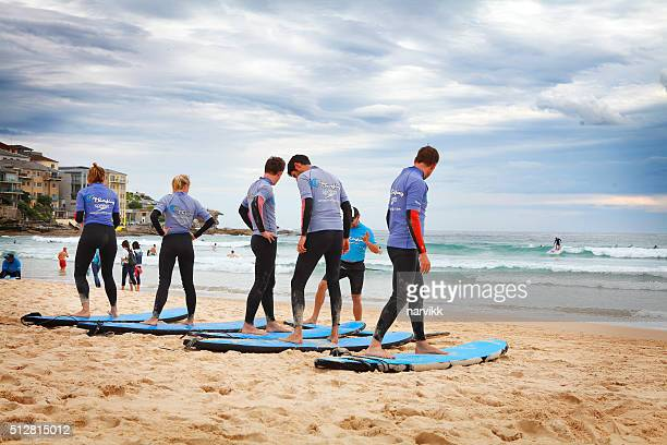 Instructor teaching people how to use surfboard