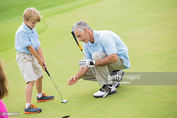 Instructor teaching young students to play golf on green