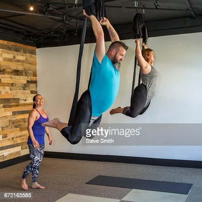 Instructor watching students performing yoga hanging from silks