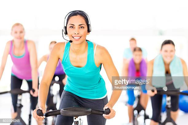 Instructor Wearing Headset Exercising With People At Health Club