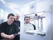Instructor with apprentices and 3D printing machine