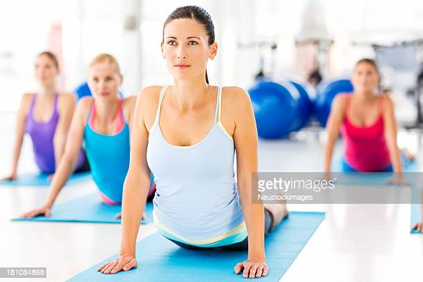 Instructor With Customers Doing Yoga Exercise In Health Club
