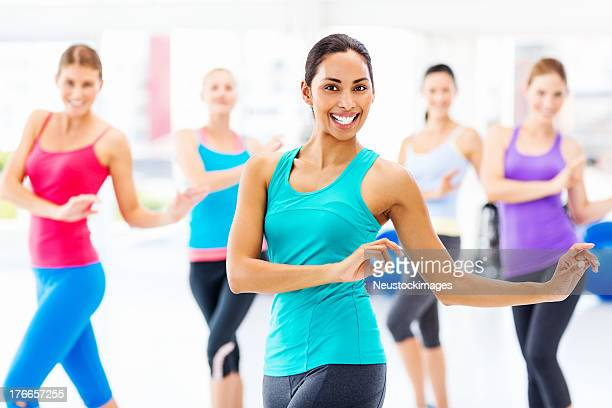Instructor With Customers Practicing Dance Fitness In Health Club