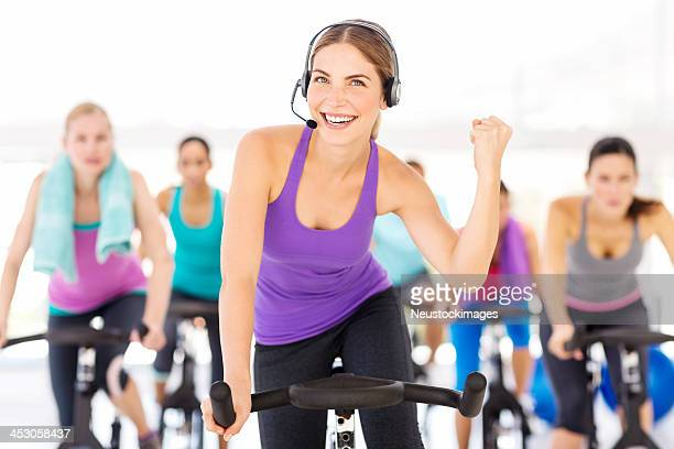 Instructor With Headset Motivating People While Exercising In Gym