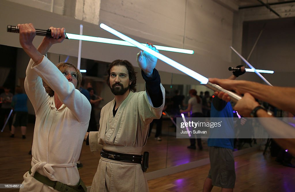 Instructors Alain Bloch assists Chandra Gilmore with her lightsaber during a Golden Gate Knights class in saber choreography on February 24 2013 in...