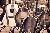 5 stringed instruments sit on a stage ready to be played.