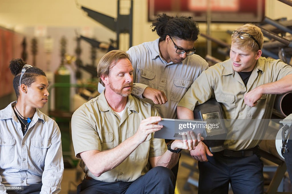 Instuctor and students in technical training school : Stock Photo