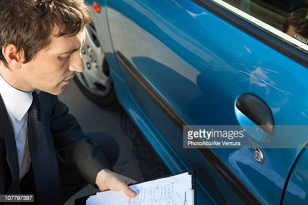 Insurance adjuster examining damage to car exterior