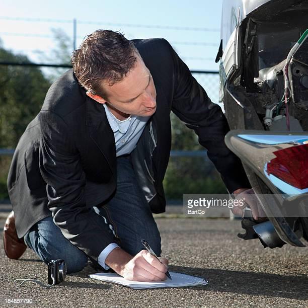 Insurance adjuster inspecting car, claim form