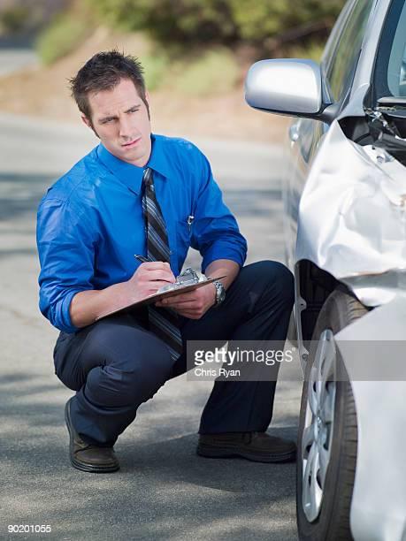 Insurance adjuster looking at damaged car