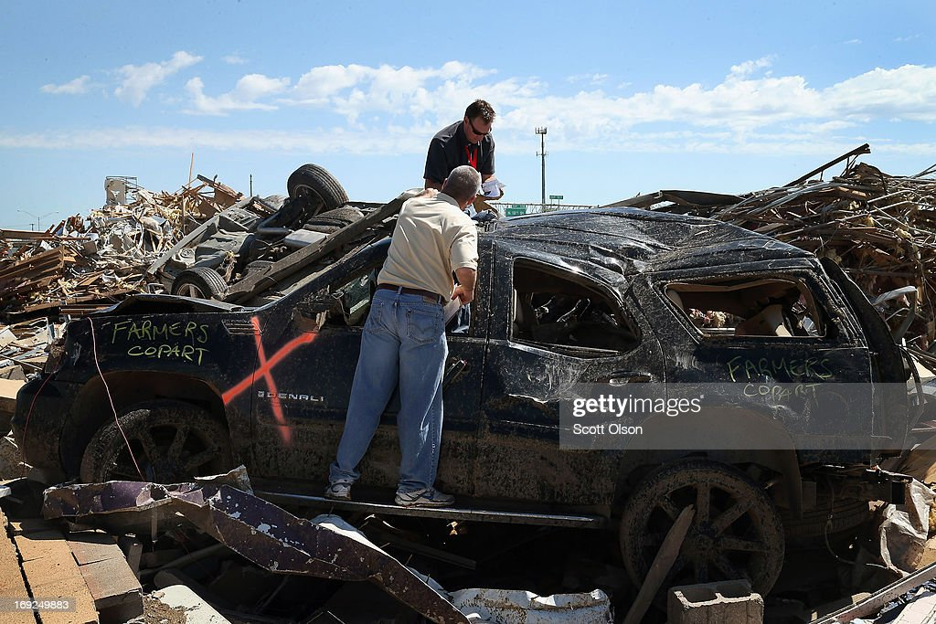 Insurance adjusters inspect damage to a vehicle that came to rest on debris of a collapsed strip mall along the I35 commercial strip after a tornado ripped through the area on May 22, 2013 in Moore, Oklahoma. The tornado of at least EF5 strength and two miles wide touched down May 20 killing at least 24 people and leaving behind extensive damage to homes and businesses. U.S. President Barack Obama promised federal aid to supplement state and local recovery efforts.