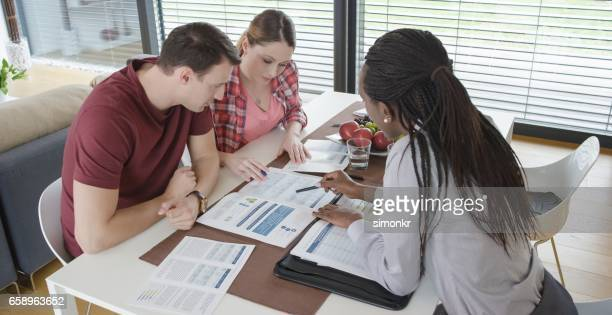 Insurance agent consulting couple in their home