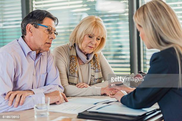 Insurance agent presenting contract to mature couple