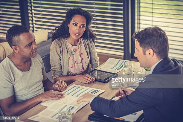 Insurance agent talking to a couple in their home