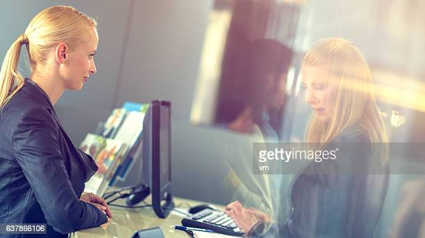 Insurance agent typing a woman's info into the computer
