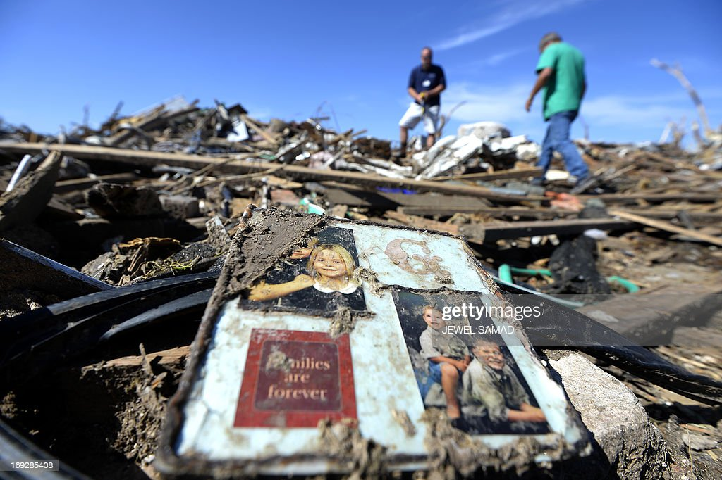 Insurance company employee David Ridge (C) inspects a client's tornado devastated home on May 22, 2013 in Moore, Oklahoma. As rescue efforts in Oklahoma wound down, residents turned to the daunting task of rebuilding a US heartland community shattered by a vast tornado that killed at least 24 people. The epic twister, two miles (three kilometers) across, flattened block after block of homes as it struck mid-afternoon on May 20, hurling cars through the air, downing power lines and setting off localized fires in a 45-minute rampage. AFP PHOTO/Jewel Samad