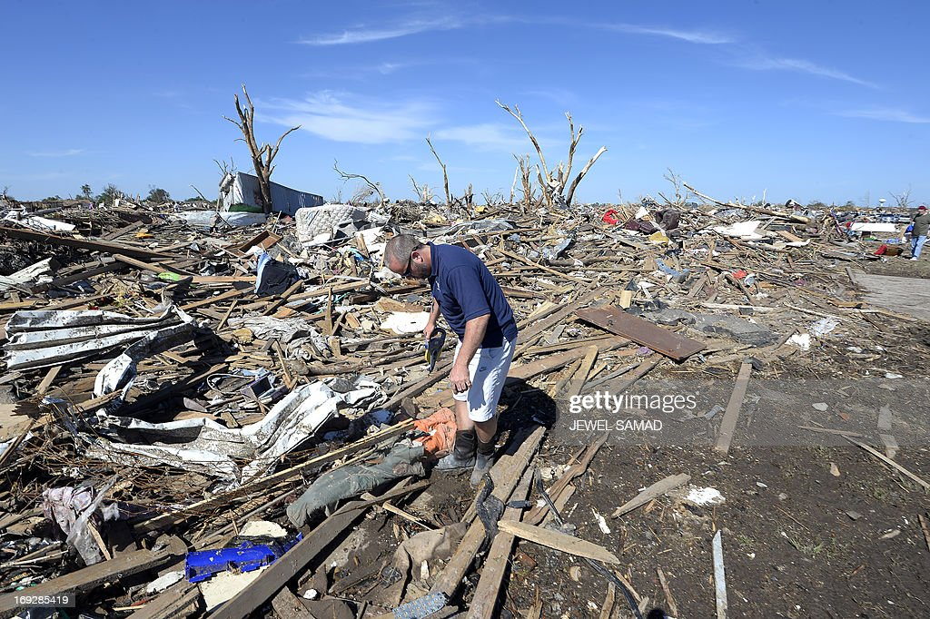 Insurance company employee David Ridge inspects a client's tornado devastated home on May 22, 2013 in Moore, Oklahoma. As rescue efforts in Oklahoma wound down, residents turned to the daunting task of rebuilding a US heartland community shattered by a vast tornado that killed at least 24 people. The epic twister, two miles (three kilometers) across, flattened block after block of homes as it struck mid-afternoon on May 20, hurling cars through the air, downing power lines and setting off localized fires in a 45-minute rampage. AFP PHOTO/Jewel Samad