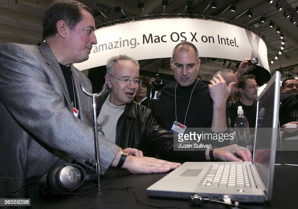 Intel CEO Paul Otellini former Intel CEO Andy Grove and Apple CEO Steve Jobs look at a new MacBook Pro laptop with Intel Core Duo processor during...