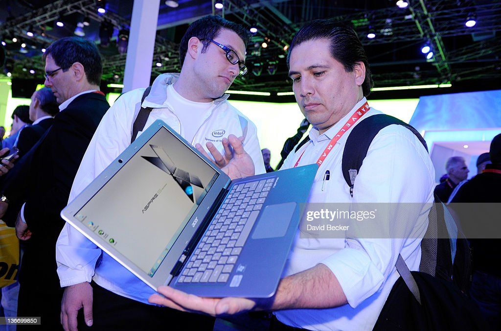 Intel representative Greg Floyd (L) assists conference attendee Alfredo Arredondo as he examines an Acer Ultrabook on at the Intel booth at the 2012 International Consumer Electronics Show at the Las Vegas Convention Center January 10, 2012 in Las Vegas, Nevada. CES, the world's largest annual consumer technology trade show, runs through January 13 and is expected to feature 2,700 exhibitors showing off their latest products and services to about 140,000 attendees.