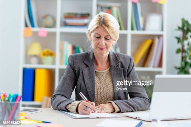 Intelligent woman in office, signing relevant documents