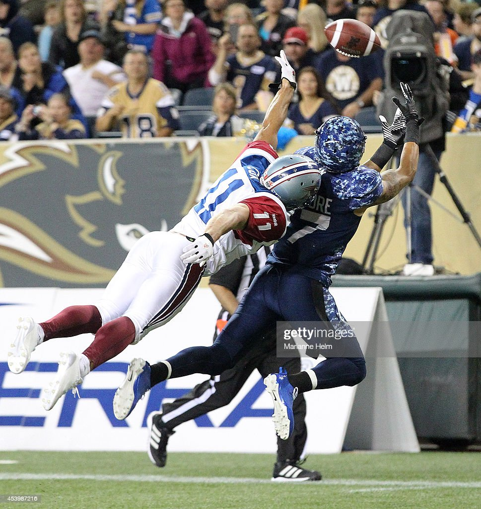 Intended receiver Nick Moore #17 of the Winnipeg Blue Bombers tries to reach the ball in the end zone under pressure by Chip Cox #11 of the Montreal Alouettes in second half action in a CFL game at Investors Group Field on August 22, 2014 in Winnipeg, Manitoba, Canada.