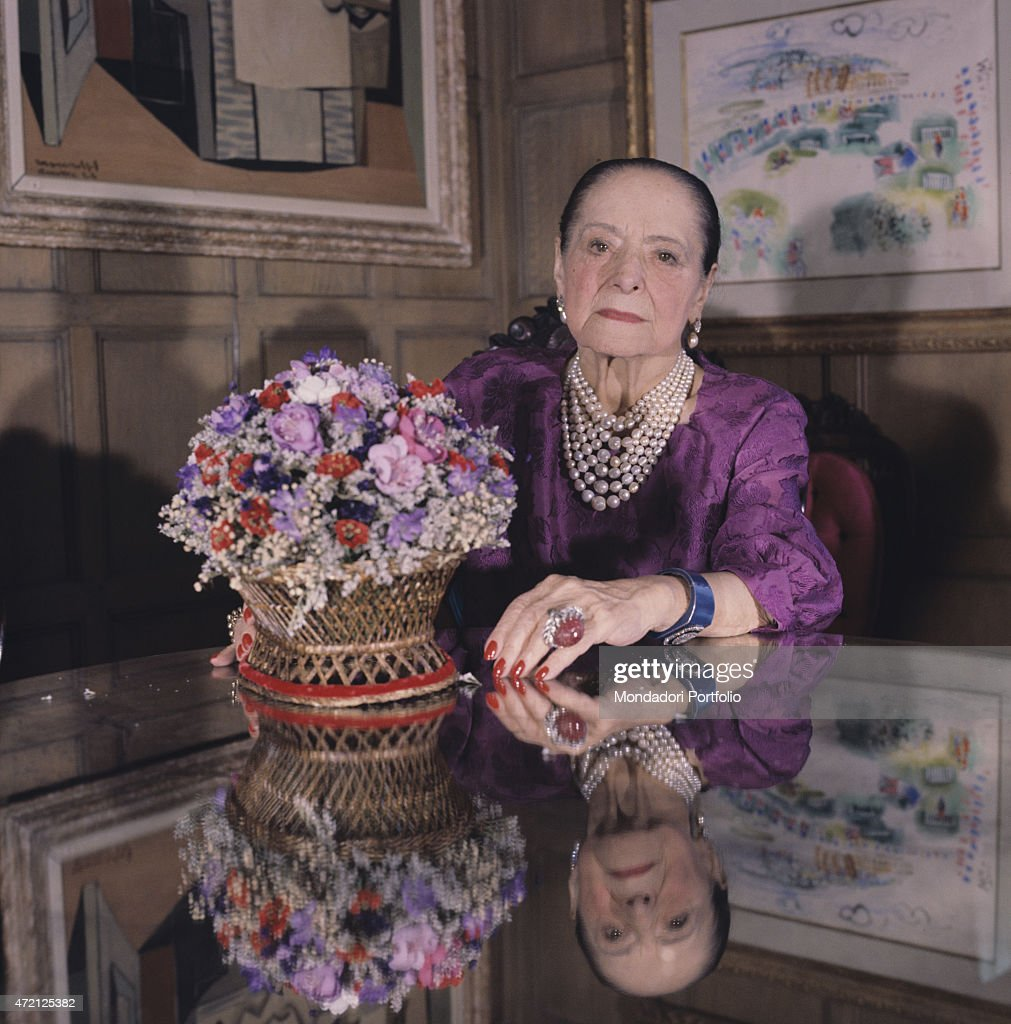 'Intense portrait of Helena Rubinstein seated on a chair with a china cup in hand the famous Polish born American entrepreneur of cosmetics...
