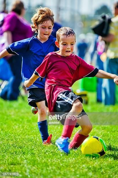 Intense Soccer Playing Boys Battle for Yellow Soccer Ball