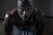 portrait of an athlete during an intense workout. African American muscular man dripping sweat