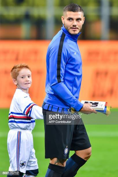 Inter Milan captain Mauro Icardi holds a copy of 'The Diary of Anne Frank' before to give it to child mascot accompanying him onto the pitch at the...