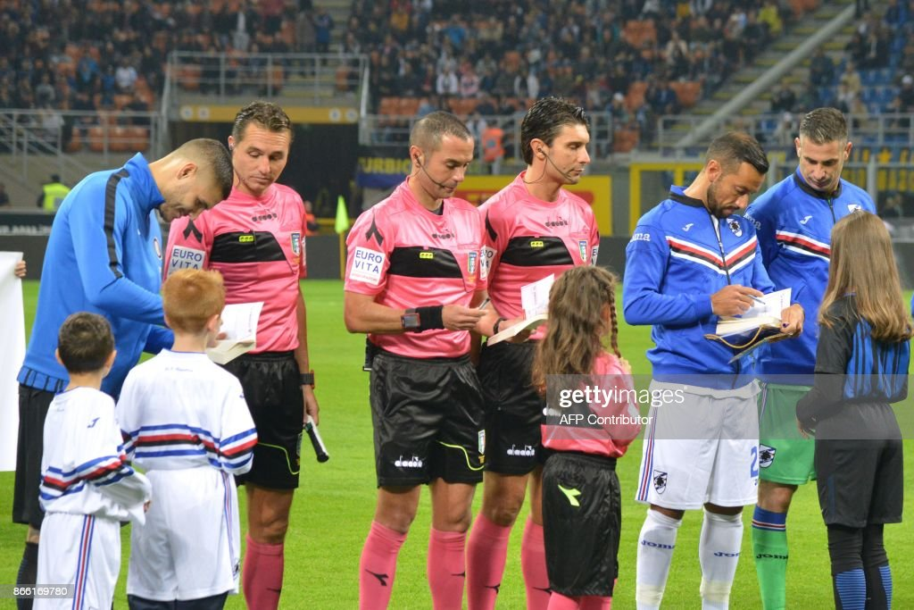 Inter Milan captain Mauro Icardi (L), Sampdoria counterpart Fabio Quagliarella (2ndR) and referee Marco Guida (C) sign copies of 'The Diary of Anne Frank' and Italian Jewish writer Primo Levi's memoir 'If This Is A Man' to child mascots accompanying players onto the pitch at the San Siro stadium prior the Italian Serie A football match Inter Milan vs Sampdoria on October 24, 2017 in Milan. The initiative followed the controversy ignited after Lazio fans defaced the Stadio Olimpico, which they share with rivals Roma, during Sunday's league game against Cagliari with anti-semitic slogans and stickers showing images of Frank. / AFP PHOTO / Paolo RATTINI