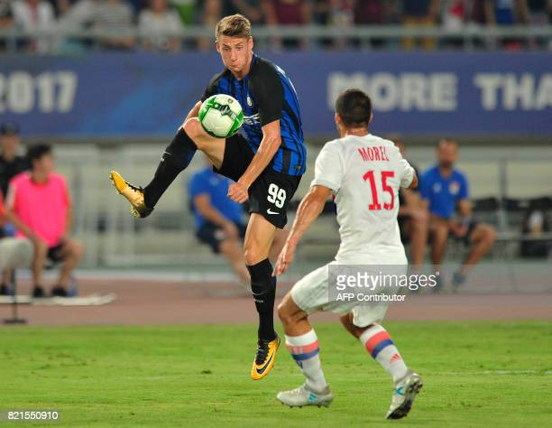 Inter Milan's Andrea Pinamonti vies for the ball with Lyon's Jeremy Morel during their International Champions Cup football match in Nanjing in...