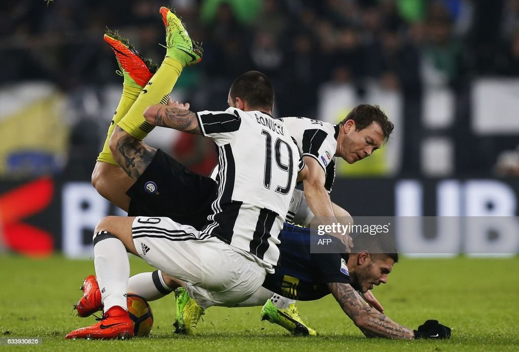 TOPSHOT - Inter Milan's Argentinian forward Mauro Icardi from (C) falls as he vies for the ball with Juventus' Italian defender Leonardo Bonucci (L) and Juventus' Swiss defender Stephan Lichtsteiner during the Italian Serie A football match between Juventus and Inter Milan on February 5, 2017 at the Juventus Stadium in Turin. / AFP PHOTO / Marco BERTORELLO