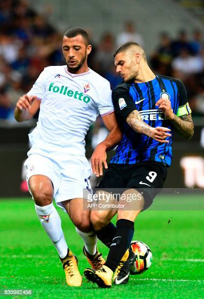 Inter Milan's Argentinian forward Mauro Icardi vies with Fiorentina's Brazilian defender Victor Hugo during the Italian Serie A football match Inter...