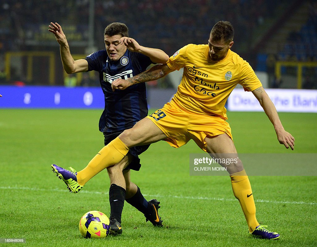 Inter Milan's Croatian midfielder Mateo Kovacic (L) fights for the ball with Hellas Verona's defender Fabrizio Cacciatore during the serie A football match Inter Milan vs Verona, on October 26, 2013 in San Siro stadium in Milan.