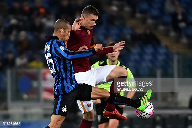 Inter Milan's defender from Brazil Joao Miranda vies with Roma's forward from BosniaHerzegovina Edin Dzeko during the Italian Serie A football match...