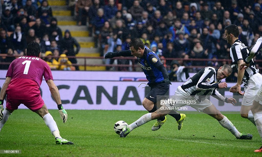 Inter Milan's forward Antonio Cassano (C) fights for the ball with Juventus' defender Giorgio Chiellini during the Italian serie A football match between Inter Milan and Juventus, on March 30, 2013 at the San Siro stadium in Milan.