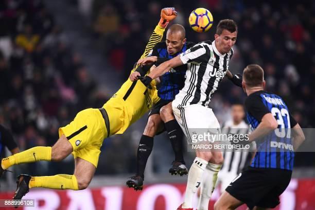 TOPSHOT Inter Milan's goalkeeper Samir Handanovic from Slovenia and Inter Milan's defender Joao Miranda de Souza Filho from Brazil fight for the ball...