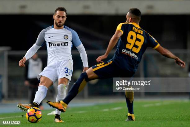 Inter Milan's Italian defender Danilo D'Ambrosio vies with Hellas Verona's French forward Mohamed Fares during the Italian Serie A football match...