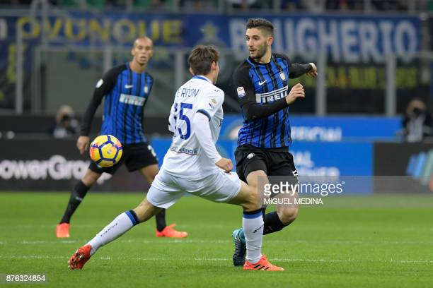 Inter Milan's Italian midfielder Roberto Gagliardini passes the ball under pressure from Atalanta's Dutch midfielder Marten de Roon during the...
