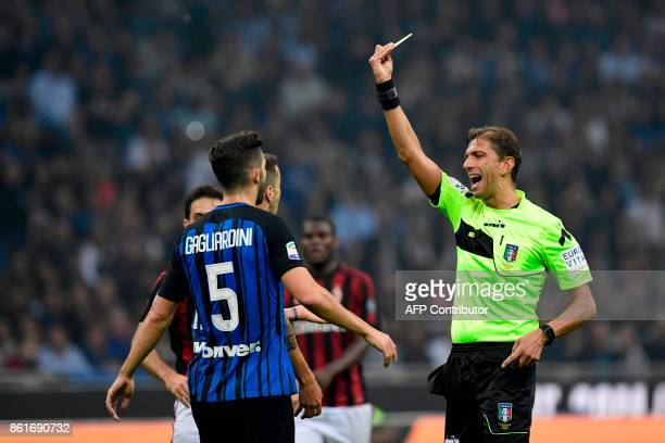 Inter Milan's Italian midfielder Roberto Gagliardini receives a yellow card from Referee Paolo Tagliavento during the Italian Serie A football match...
