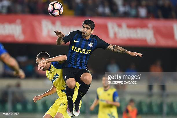 Inter Milan's midfielder from Argentina Ever Banega vies for the ball with Chievo's midfielder from Serbia Ivan Radovanovic during Italian Serie A...
