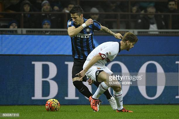 Inter Milan's midfielder from Montenegro Stevan Jovetic fights for the ball with Genoa's defender from Italy Cristian Ansaldi during the Italian...