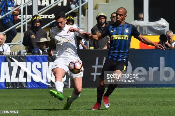 Inter Milan's midfielder from Portugal Joao Mario fights for the ball with AC Milan's midfielder from Argentina Jose Sosa during the Italian Serie A...