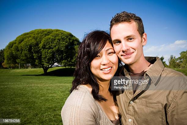Interatial couple portrait taken at a park