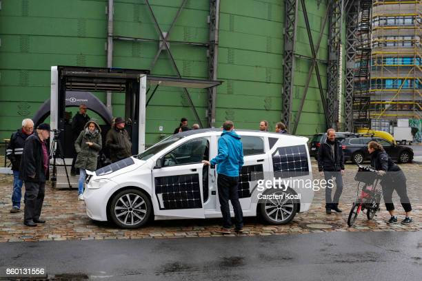 Interested people look on a Sono Motors Sion solarpowered electric car during a presentation event on October 11 2017 in Berlin Germany Munichbased...