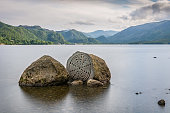 A photograph of two interesting rocks with a beautiful cloudy sky in the background. Taken at Derwentwater in Keswick, fells such as Cat Bells can be seen in the background.